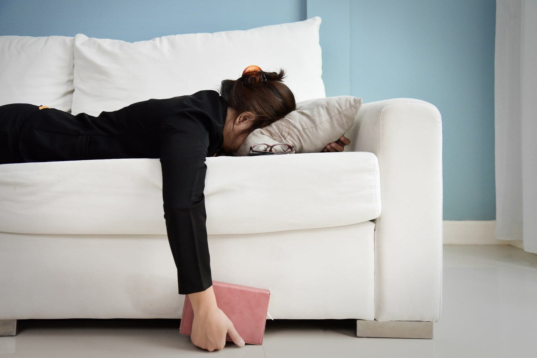 Exhausted, Tired Asian Business woman in black shirt holding notebook and sleeping on white sofa with blue wall. Stress from overtime working concept.